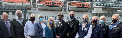 Princess Cruises Shore Power Event speakers and attendees take photo in front of Majestic Princess on Franklin Street Dock Sea Walk in Juneau.